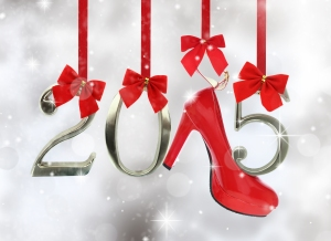 High heel shoe and 2015 number hanging on red ribbons in a glitt