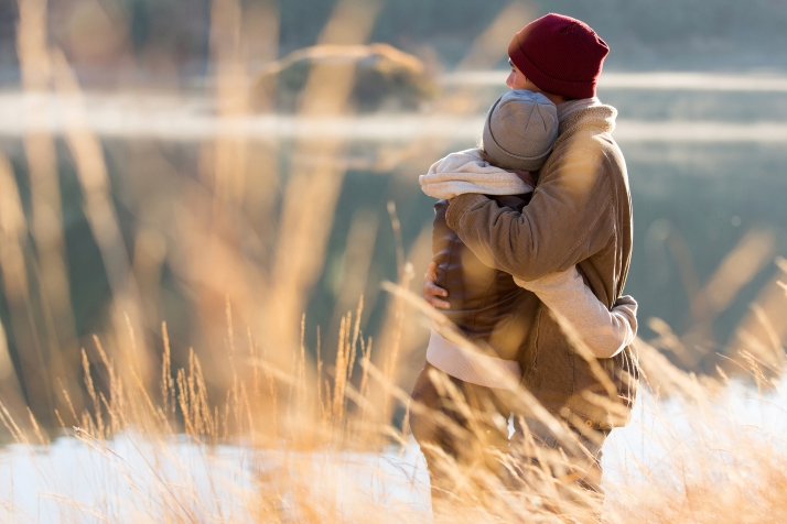 back view of lovely young couple hugging in winter