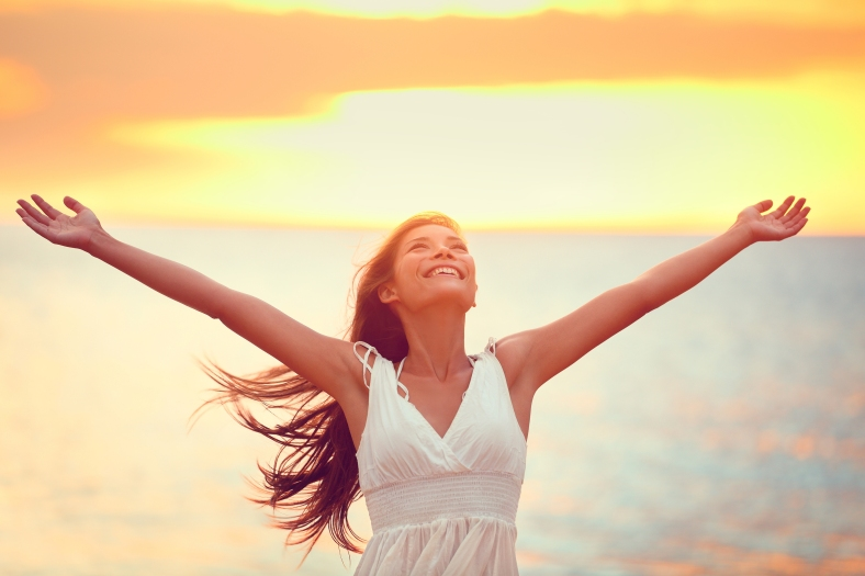 Free happy woman arms up praising freedom at beach sunset. Young